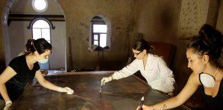 Imagen de varias restauradoras de la Fundación Tarazona Monumental, restaurando un lienzo.
