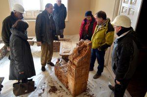 Técnicos encargados de la rehabilitación del Palacio, observando una zapata de madera del edificio.