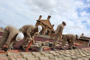 Alumnos trabajando en la colocación de tejas.